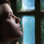 Beautiful girl reaches for the light in the window. Beautiful profile and light